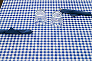 restaurant table setting with two glasses and cutlerly