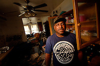 """I live here with me, my wife, my 2 daughters, my 2 sons, and 6 grandchildren. I evacuated from Austin, TX, Dallis, TX, Columbia, Miss, and back to New Orleans where I will rebuild my house and will stay.""  ..Resident of the lower 9th Ward in New Orleans, Lawrence Hamilton's, home was destroyed by floodwaters following Hurricane Katrina two months prior. (Robert Caplin/New York Times)..."