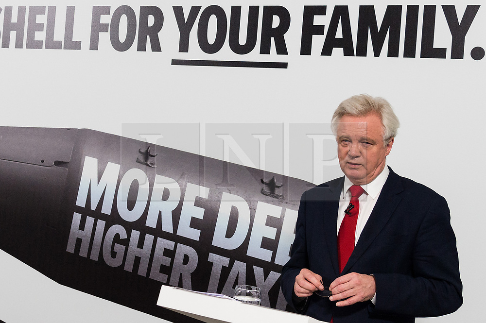"""© Licensed to London News Pictures. 03/05/2017. London, UK.  DAVID DAVIES Secretary of State for Exiting the European Union speaks at a General Election Campaign event featuring a poster of Labour party leader JEREMY CORBYN with the slogan """"More debt, higher tax."""" Photo credit: Ray Tang/LNP"""
