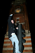Teenager triumphantly holds his hands in the air, proud of climbing atop some traffic lights, UK, 2000's