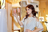 Beautiful woman looking at price tag of lighting fixture with hand on hip while standing in lights store