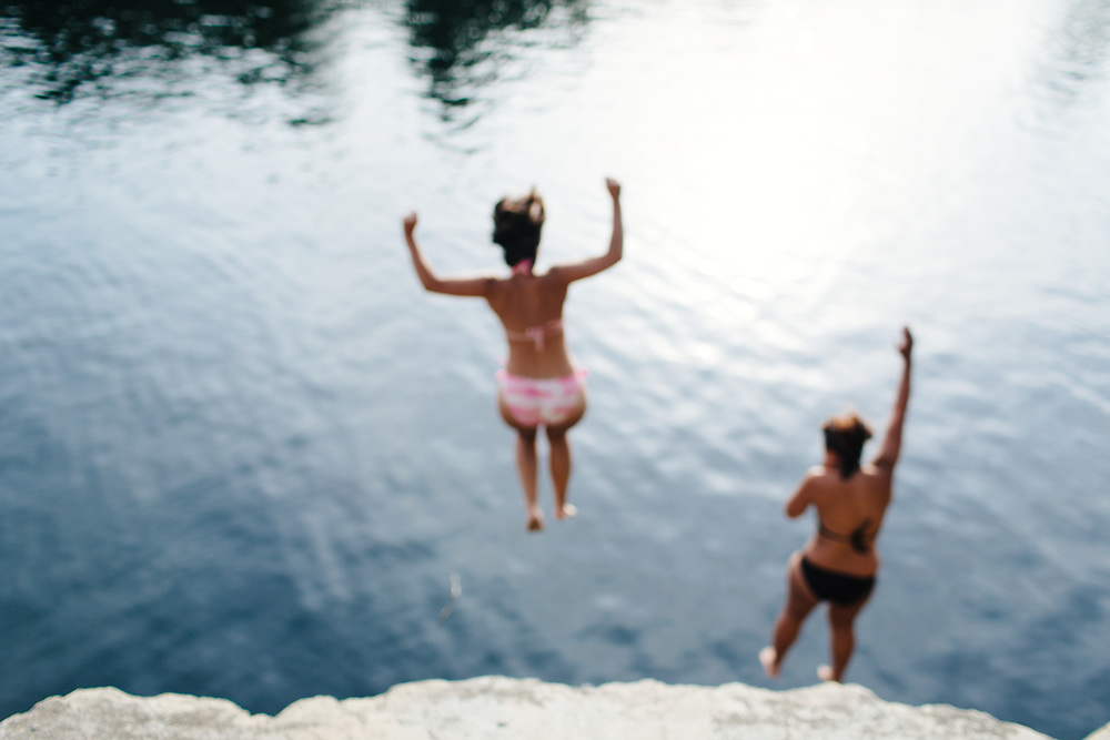 Young women jumping into quarry