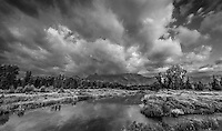 A monochrome view of Schwabacher Landing in Grand Teton National Park with some dramatic clouds covering the mountain range.