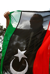 A protestor holds a Kingdom of Libya flag during a protest outside the Libyan Embassy in Attard, outside Valletta, February 22, 2011. The protest was organised by the Libyan community living in Malta against the Libyan government's crackdown on demonstrators in Libya..Photo by Darrin Zammit Lupi