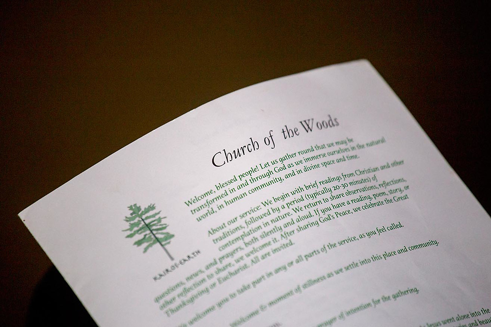 A worshiper looks at the bulletin for the afternoon service at Church of the Woods in Canterbury, N.H., on April 30, 2017. The Episcopal church, established in 2014, holds two outdoors services every Sunday. (Photo by Geoff Hansen)