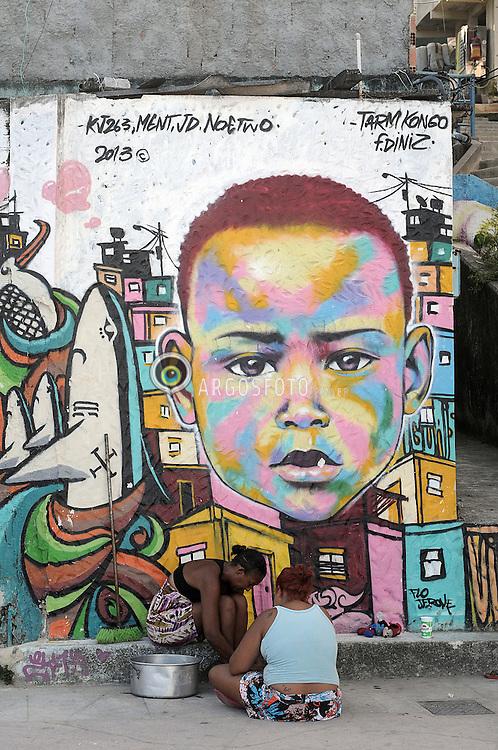Moradoras em frente a grafite na Favela do Vidigal . / Residents in front of graffiti in the Vidigal favela. Ano 2014.Rio de Janeiro.Foto Christian Tragni/Argosfoto