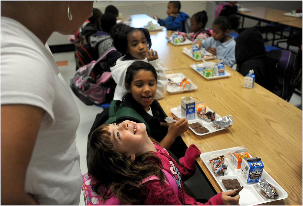 Brianna Bryant smiles at a teacher while eating breakfast.  The cafeteria fills up each morning at Ball with students who qualify for free or reduced-price meals.