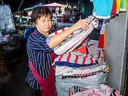 12 JANUARY 2017 - BANGKOK, THAILAND: A vendor sorts clothes in her shop in Bo Bae Market. Bo Bae Market is a sprawling wholesale clothing market in Bangkok. There are reportedly more than 1,200 stalls selling clothes made in Thailand and neighboring countries. Bangkok officials have threatened to shut down parts of Bo Bae market, but so far it has escaped the fate of the other street markets that have been shut down.     PHOTO BY JACK KURTZ