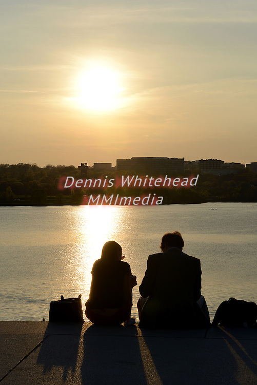 A couple pause to look over the Potomac River atop the Watergate in Washington, DC, looking toward Virginia, silhouetted by the setting sun.