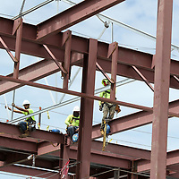 Workers secure a steel truss into place on the new student services building under construction at the Tupelo Campus on Tuesday afternoon.