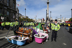 © Licensed to London News Pictures. 10/10/2019. London, UK. Items, including a bath and a piano, belonging to Extinction Rebellion activists lie in the road around Trafalgar Square in Westminster, central London where campaigners have been demonstrating for a fourth day running. The climate change group have blockaded the Westminster area, demanding that the government takes immediate and decisive action on climate change. Photo credit: Ben Cawthra/LNP
