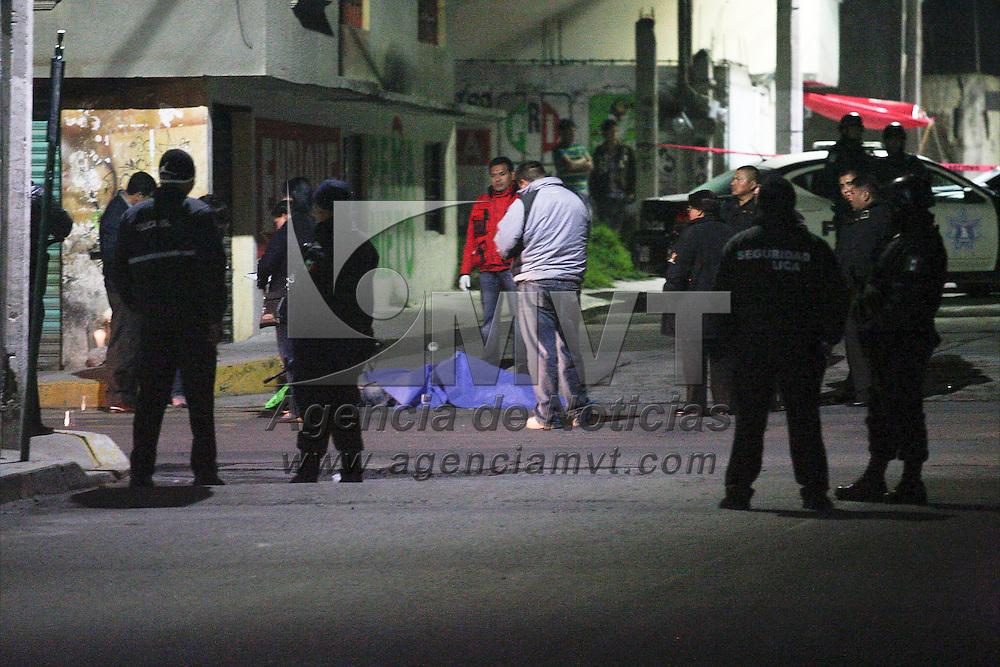 TOLUCA, Mexico.- Peritos de la PGJEM analizan y levantan evidencias del lugar donde fue asesinado, de multiples disparos, un hombre de aprox 35 anos, los himicidas a sus pies dejaron un mensaje, la policia municipal por su parte resguardo el perimetro de la esquina de Roque Gonzalez y Laguna de Guzman en la colonia 8 Cedros. Agencia MVT / Staff.