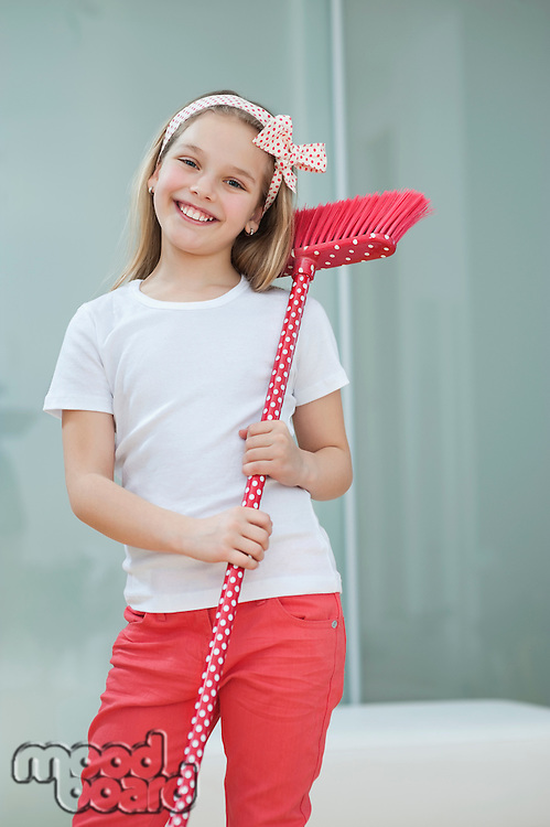 Portrait of a happy young girl with broom