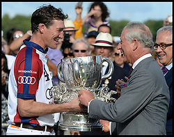 HRH The Prince of Wales hands over the winning trophy to the England Captain Luke Tomlinson after England beat The USA in the  Audi International Polo 2013-Westchester Cup Polo match Audi England v Equus & Co USA at the <br /> Guards Polo Club, Egham, United Kingdom,<br /> Sunday, 28th July 2013<br /> Picture by Andrew Parsons / i-Images