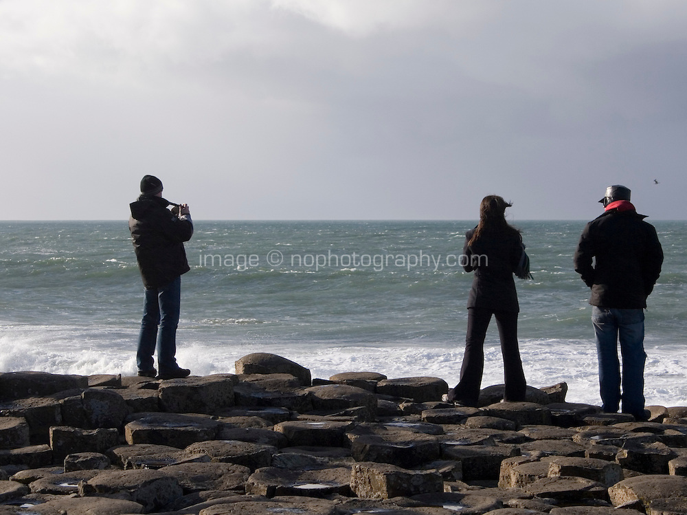 Tourists at the Giants Causeway geological phenomenon with hexagonal columns formed by lava cooling during Tertiary period in Antrim Northern Ireland