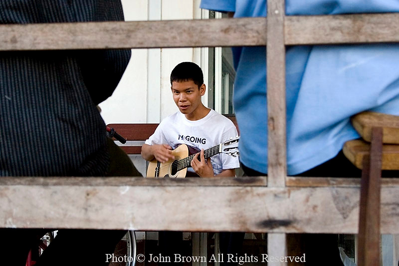A 16 year old Asian boy who is a hospital patient is enjoying music as therapy by playing a guitar at the Dormitory and Treatment Wing of the National Rehabilitation Center in Vientiane, Laos.