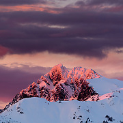 The sun turns the peaks of the Cascades crimson as evening approaches in the Mount Baker backcountry.
