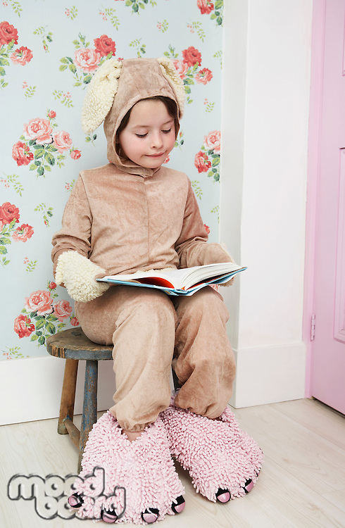 Young girl (5-6) sitting on stool reading wearing bunny costume and monster slippers