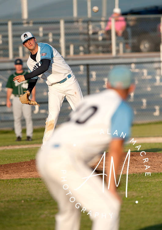 Muskrats' pitcher Kyle Owings fires a pick off throw to first baseman Adam Kirsch during Monday's game against the Vermont Mountaineers at Laconia's Robbie Mills Memorial Sports Complex.  (Alan MacRae/for the Citizen)