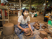 02 NOVEMBER 2014 - TWANTE, YANGON DIVISION, MYANMAR:  A worker forms clay into blocks that other workers will use to make pots in a pottery factory in Twante, Myanmar. Twante, about 20 miles from Yangon, is best known for its traditional pottery. The pottery makers are struggling to keep workers in their sheds though. As Myanmar opens up to outside investments and its economy expands, young people are moving to Yangon to take jobs in the better paying tourist industry or in the factories that are springing up around Yangon.   PHOTO BY JACK KURTZ