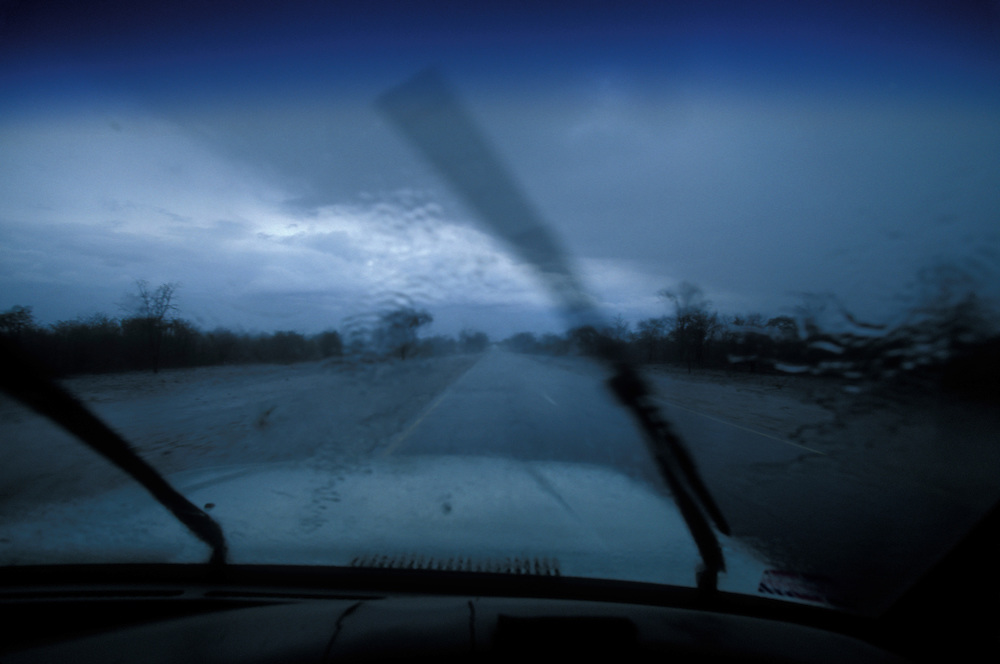 Africa, Botswana, Palapye, View through Land Cruiser safari truck's windshield of torrential rain storm in Kalahari Desert