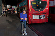 A man on crutches stands looking at his smartphone as a bus advertising Boots the Chemist drives past, on 9th December 2016 in Southwark, London, England.