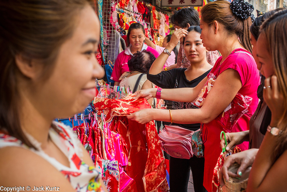 "22 JANUARY 2013 - BANGKOK, THAILAND:   Women shop for new dresses for Chinese New Year at pop up stores on Yaowaraj (Yaowarat) Road, the heart of Bangkok's Chinatown district. Chinese New Year is not an official public holiday in Thailand, but it is one the biggest celebrations in the Bangkok, which has a large Chinese population. Chinese New Year is February 10 this year. It will be the ""Year of the Snake.""    PHOTO BY JACK KURTZ"