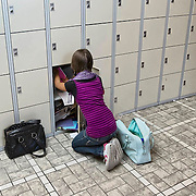 Nederland Rotterdam 23-09-2009 20090923 Serie over onderwijs,  openbare scholengemeenschap. Leerlinge wisselt boeken bij de lockers. Tussen de lesuren.                                 .Foto: David Rozing