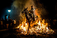 """A man rides a horse through a bonfire as part of a ritual in honor of Saint Anthony the Abbot, the patron saint of domestic animals, in San Bartolome de Pinares, Spain, Saturday, Jan. 16, 2016. On the eve of Saint Anthony's Day, dozens ride their horses through the narrow cobblestone streets of the small village of San Bartolome during the """"Luminarias,"""" a tradition that dates back 500 years and is meant to purify the animals with the smoke of the bonfires and protect them for the year to come."""