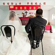 Bride and groom sit and listen to pastors speech during their wedding ceremony. Namasiya Township, Kaoshiung County, Taiwan
