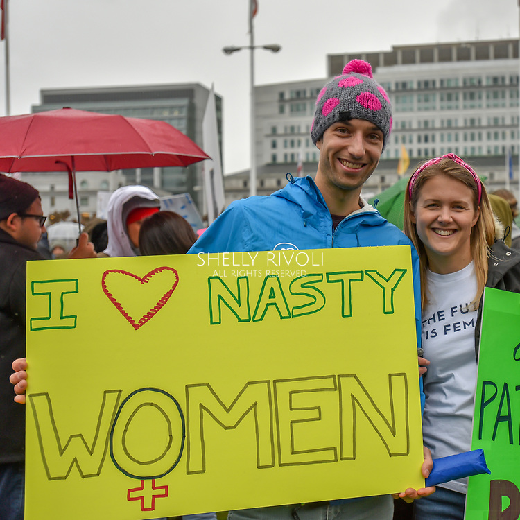 "A young man at the pre-march rally holds a sign reading, ""I love (heart) nasty women."""