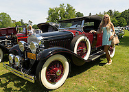 Old Westbury, New York, U.S. - June 1, 2014 -  Visitor AGNES PIETRYKA, of Brooklyn, poses by a red and black 1927 La Salle 303 Roadster, owned by JOHN MICCICHE of SMITHTOWN, which is an entry at the Antique and Collectible Auto Show held on the historic grounds of elegant Old Westbury Gardens in Long Island, and sponsored by Greater New York Region AACA Antique Automobile Club of America.
