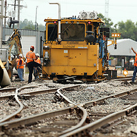 A BNSF work crew works on the rails at Green Street on Tuesday in Tupelo.