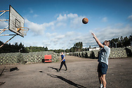 Soldiers play basketball inside the military encampment of  Rukla's military base.  In Lithuania, Basket is incredibly popular.