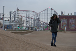 "© Licensed to London News Pictures . 10/12/2014 . Blackpool , UK . A man pulls his hood up in the face of high winds on Blackpool Promenade . An explosive cyclogenesis - a fast developing storm in which air pressure falls rapidly - known as a "" weather bomb "" - hits the North of England , bringing storms to the region . Photo credit : Joel Goodman/LNP"