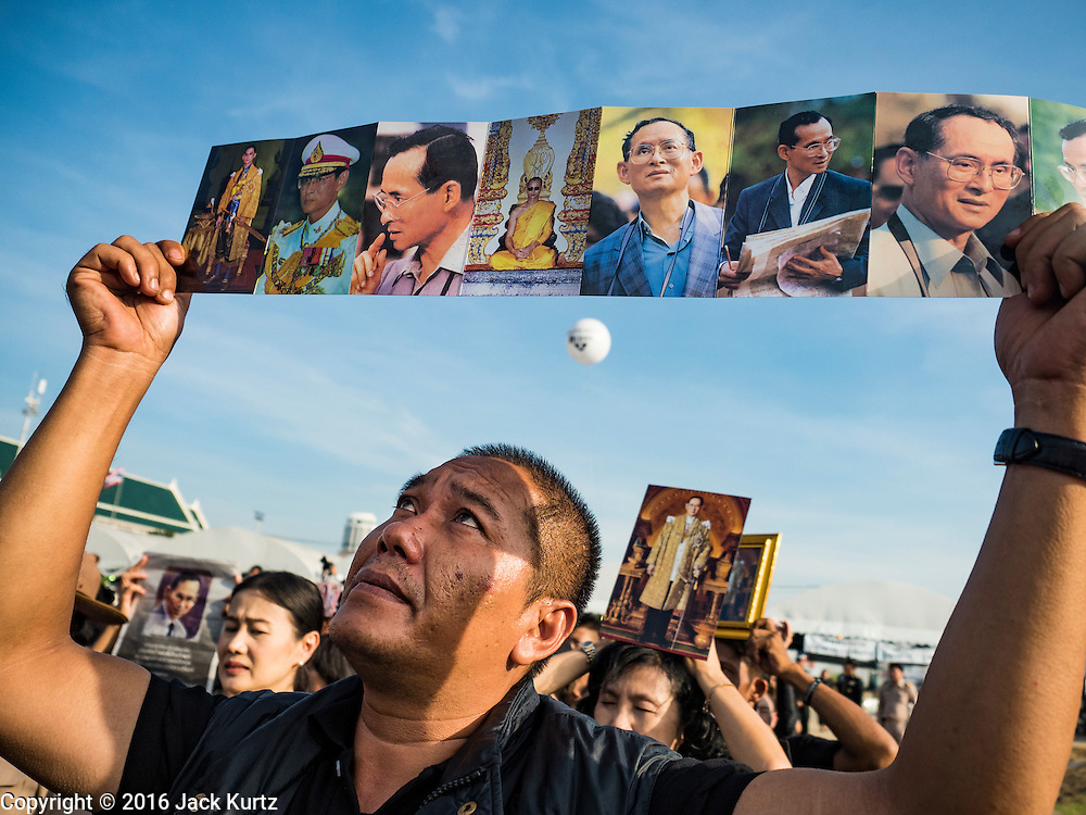 22 NOVEMBER 2016 - BANGKOK, THAILAND: A man at Sanam Luang holds up post card booklet of photos of Bhumibol Adulyadej, the Late King of Thailand, during a ceremony to honor His Majesty. Hundreds of thousands of Thais gathered across Thailand Tuesday to swear allegiance to the Chakri Dynasty in a ceremony called Ruam Phalang Haeng Kwam Phakdi (the United Force of Allegiance). At Sanam Luang, the Royal Parade Ground, and location of most of the mourning ceremonies for the late King, people paused to honor His Majesty by singing the Thai national anthem and the royal anthem.       PHOTO BY JACK KURTZ
