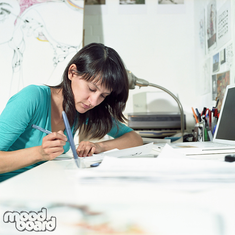 Young female illustrator working in home office