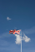 The British Union Jack Flag flies in a stiff breeze, its colours of red-white and blue almost wholly horizontal as the wind tears through the blue skies and beneath wispy cirrus clouds, in Eastbourne, West Sussex, England UK. Tied to its flag-pole, this symbol of patriotic nationalism, evokes a sense of pride and spirit the British are known for - having encouraged them through two world wars and more recently, other military campaigns. The colours (colors) of Scotland's blue and white crosses and the English cross of St. George are merged to make this well-known symbol of the British Isles.