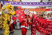 "10 FEBRUARY 2013 - BANGKOK, THAILAND: A Laughing Buddha and Lion Dancers perform on Yaowarat Road on Chinese New Year in Bangkok. Bangkok has a large Chinese emigrant population, most of whom settled in Thailand in the 18th and 19th centuries. Chinese, or Lunar, New Year is celebrated with fireworks and parades in Chinese communities throughout Thailand. The coming year will be the ""Year of the Snake"" in the Chinese zodiac.    PHOTO BY JACK KURTZ"