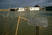 Wrecked property in a flooded caravan park in the north Welsh coast community of Towyn, UK. On the fence is the reminder of what this summer holiday site would normally be like, where owners remind holidaymakers not to hang their washing on the broken fence. A combination of gale-force winds, a high tide and rough seas caused Towyn's flood defences to be breached at about 11.00am on 26 February 1990. 4 square miles (10 km2) of land was flooded, affecting 2,800 properties and causing areas of the resort to be evacuated.