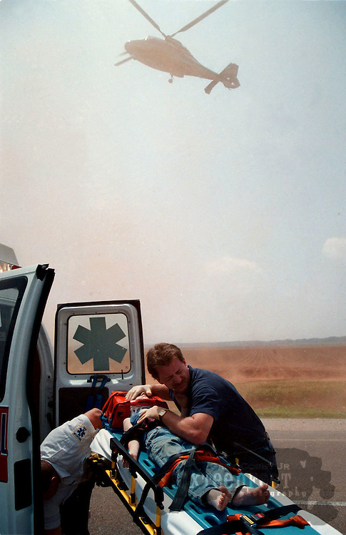 Decatur Fire and Rescue Lt. Greg Griffith covers a child injured in a triple fatality accident as a medical helicopter lands near them.  The child was the only member of his family to survive the wreck.  Photo by Gary Cosby Jr.