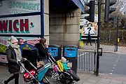 Mothers pass a question mark in the context of a billboard ad and mothers at East Dulwich, on 10th February 2019, in London, England.
