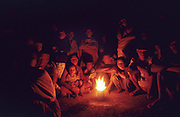 LOGGING DAYAK BLOCKADE, MALAYSIA. Sarawak, Borneo, South East Asia. Night-time, sitting around oil burner. Kenyah and Penan blockading logging road, 1991 <br /> <br /> Tropical rainforest and one of the world's richest, oldest eco-systems, flora and fauna, under threat from development, logging and deforestation. Home to indigenous Dayak native tribal peoples, farming by slash and burn cultivation, fishing and hunting wild boar. Home to the Penan, traditional nomadic hunter-gatherers, of whom only one thousand survive, eating roots, and hunting wild animals with blowpipes. Animists, Christians, they still practice traditional medicine from herbs and plants. Native people have mounted protests and blockades against logging concessions, many have been arrested and imprisoned.