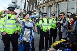 © Licensed to London News Pictures. 09/10/2019. LONDON, UK.  A woman protests in front of the police as mothers and their babies take part in The Mothers' March during day 3 of Extinction Rebellion's climate change protest in the capital.  Activists marched from Westminster Abbey to Whitehall to stage a sit-down demonstration against the effects of climate change and the future for their children.  Photo credit: Stephen Chung/LNP