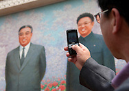 North Korea, Pyongyang District, Pyongyang, man taking a picture at kimilsungia exhibition