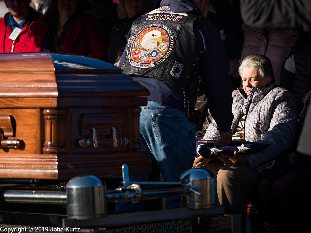 22 NOVEMBER 2019 - DES MOINES, IOWA: A member of the Patriot Guard Riders makes a presentation to the family of US Marine Reserve Corps Private Channing Whitaker during Whitaker's reinterment service in Glendale Cemetery. Whitaker died in the Battle of Tarawa on Nov. 22, 1943. He was buried on Betio Island, in the Gilbert Islands, and his remains were recovered in March 2019. He was identified by a DNA match with surviving family members in Iowa. Whitaker was reintered in the Glendale Cemetery in Des Moines exactly 76 years after his death in World War Two. About 1,000 US Marines and sailers were killed in four days during the Battle of Tarawa.            PHOTO BY JACK KURTZ