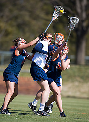 Syrcause Orange D Christina Gibson (14) reaches over Virginia Cavaliers M Brittany Kalkstein (17) for a loose ball.  The #2 ranked Virginia Cavaliers women's lacrosse team defeated the #4 ranked Syracuse Orange 13-8 at the University of Virginia's Klockner Stadium in Charlottesville, VA on March 1, 2008.