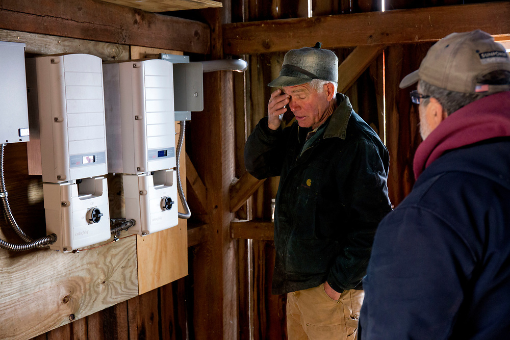Farmer Bob Gray asks Peck Electric subcontractor Jerry Houghton questions about the new solar system being installed at 4 Corners Farm in Newbury, Vt., on May 9, 2017. Gray said they decided to go ahead with the large project before the state's tax credit program expired. (Photo by Geoff Hansen)