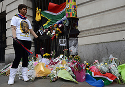 © Licensed to London News Pictures.06/12/2013. London, UK. A woman in a Nelson Mandela t-shirt stands by flowers and candles at the South African Embassy, London to pay tribute to late former South African president Nelson Mandela following his death in Johannesburg.Photo credit : Peter Kollanyi/LNP