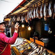 A woman takes inventory of fish at a market in Busan, South Korea.